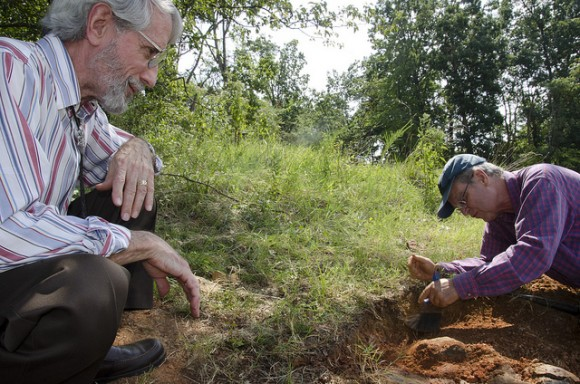 Ray Stanford, left, and Rob Weems examine the large dinosaur footprint