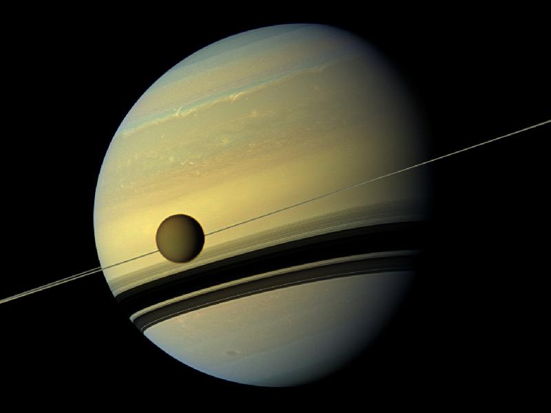 Titan appears to hang on a thread in the foreground in this amazing view of Saturn from Cassini