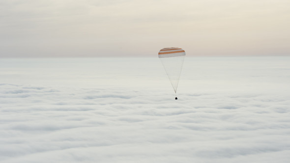 The Soyuz TMA-18M spacecraft descends above the clouds with Expedition 46 Commander Scott Kelly of NASA and Russian cosmonauts Mikhail Kornienko and Sergey Volkov of Roscosmos. Image credit: NASA/Bill Ingalls